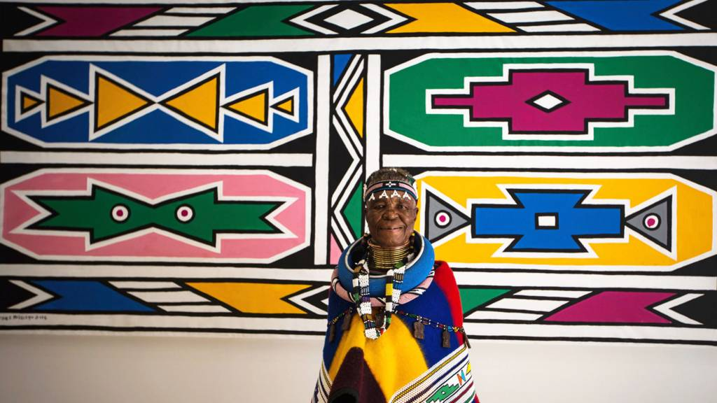South African artist Esther Mahlangu poses in front of her artwork in March 2017 at a gallery in Johannesburg
