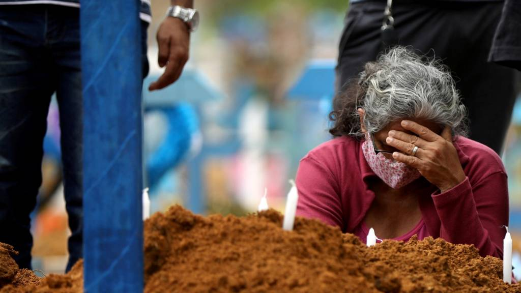 A woman attends a mass burial of victims of coronavirus at the Parque Taruma cemetery in Manaus, Brazil, 26 May 2020