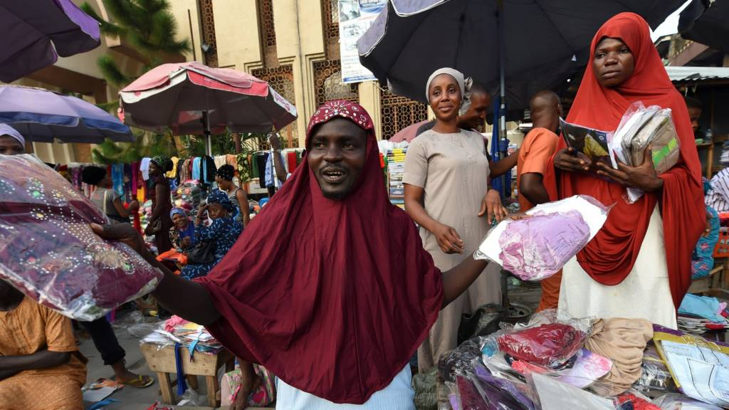 Roadside male vendor wears female hijab to advertise and market the wear to Muslims shopping to celebrate Eid el Fitr in Lagos