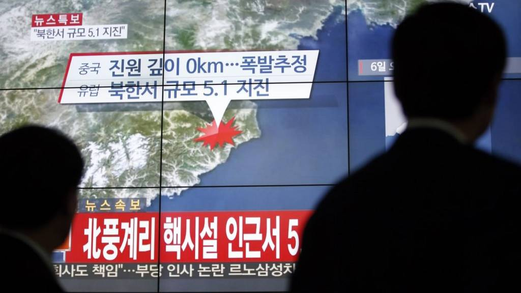 South Koreans in Seoul watch a news report on the reported test (6 Jan 2016)