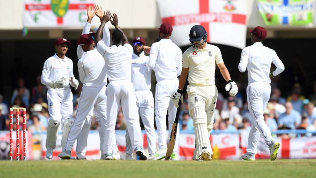 Rory Burns of England walks to the pavilion as Kemar Roach of West Indies celebrates
