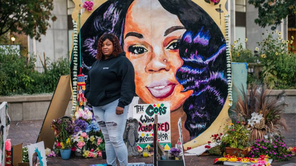 Breonna Taylor's mother stands in front of a mural with her image