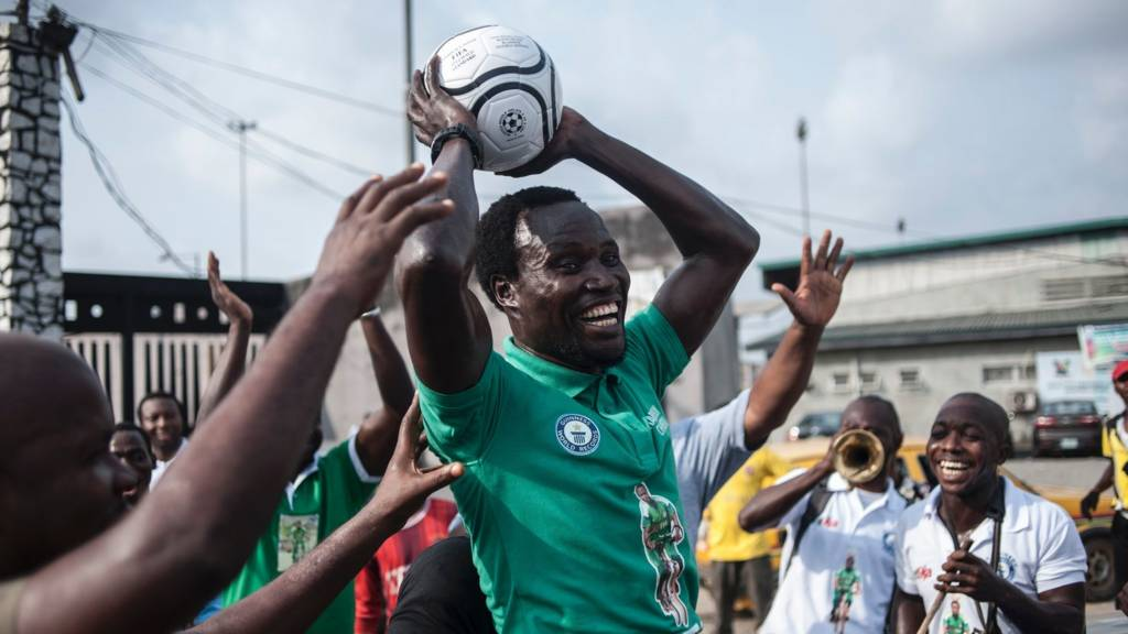 Harrison Chinedu celebrates after completing 103,6 km balancing a football on his head while riding a bicycle