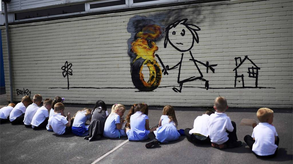 School children sit by the new Banksy mural in Bristol