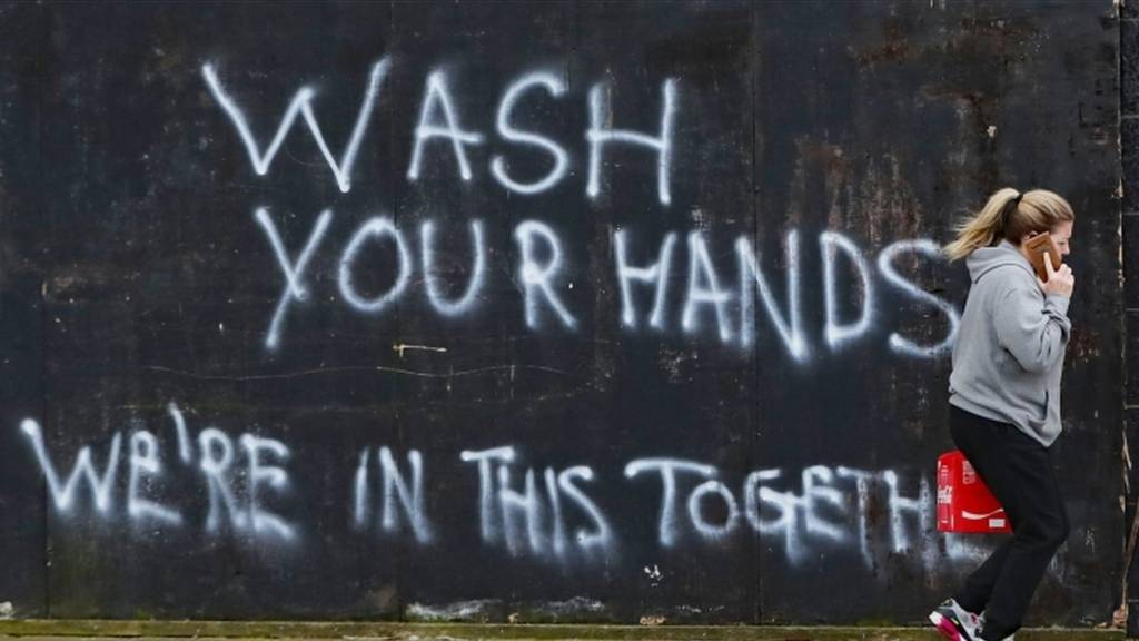 A woman walks past graffiti calling on people to wash their hands during the Covid-19