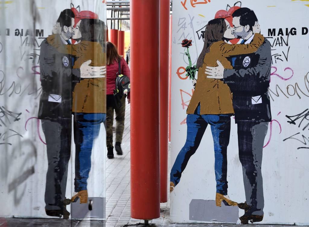 رسم جداري في أحد شوارع برشلونة يصور رئيس الوزراء الإسباني يقبل مرشحة في الانتخابات الكتالونية