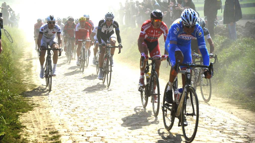 Spectators cheer riders through a cobblestoned section during the Paris-Roubaix