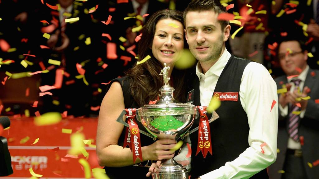 Mark Selby lifts the trophy with wife Vikki after winning The Dafabet World Snooker Championship
