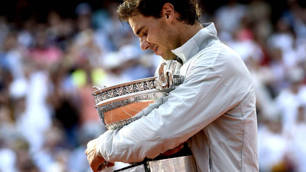 Rafael Nadal reacts as he holds the Musketeers trophy after winning the French tennis Open