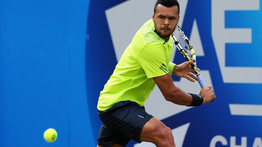 Jo-Wilfried Tsonga of France plays a backhand against David Goffin