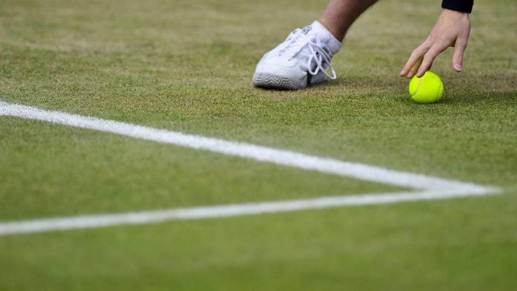 A ball boy retrieves a tennis ball during a match at Wimbledon