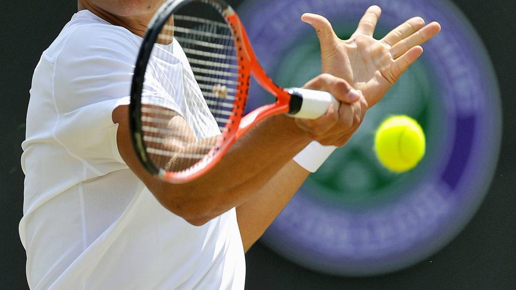 A tennis player makes a forehand shot at the Wimbledon Championships