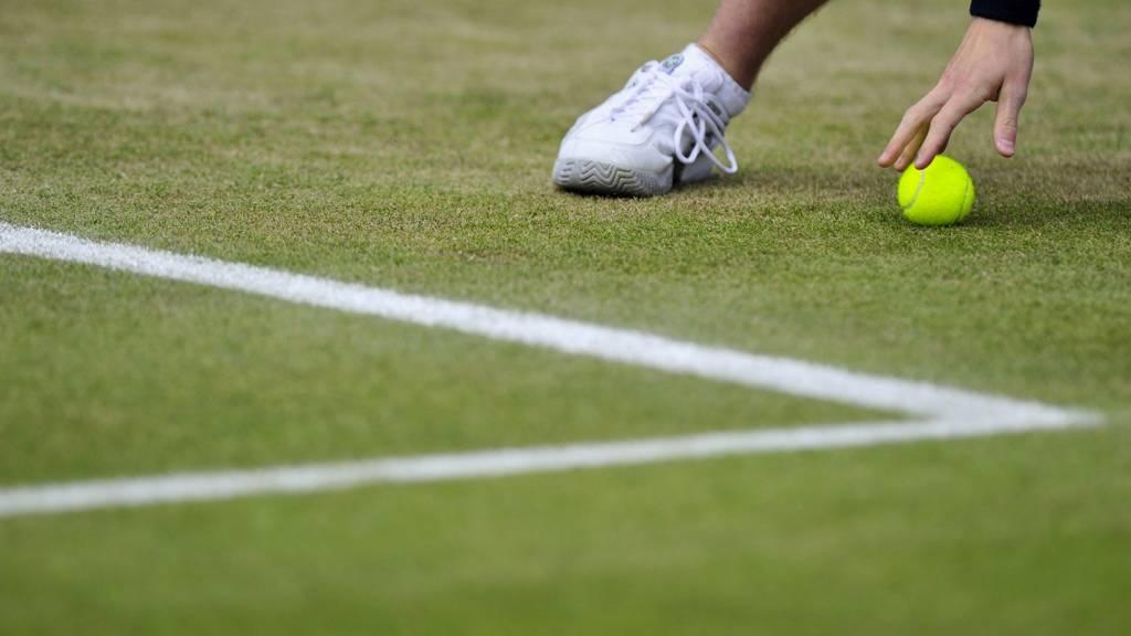 A ball boy retrieves a tennis ball at the Wimbledon Championships