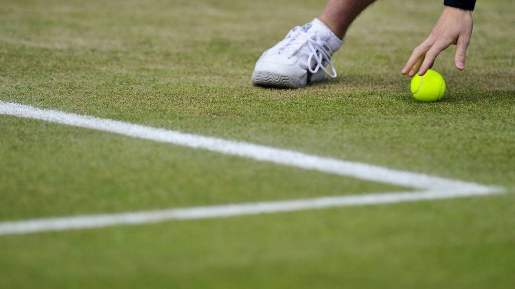 A ball boy retrieves a tennis ball at the Wimbledon Championships