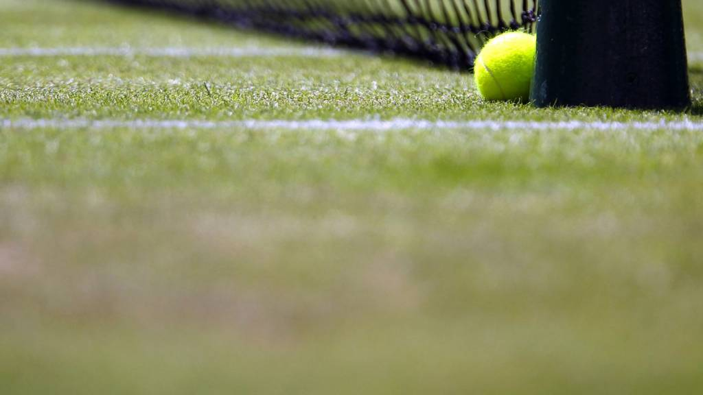 A tennis ball on a grass court at Wimbledon