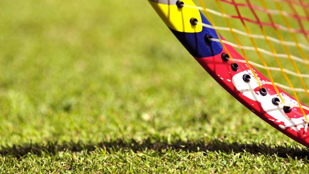 A close-up of a tennis racquet on a grass court at Wimbledon