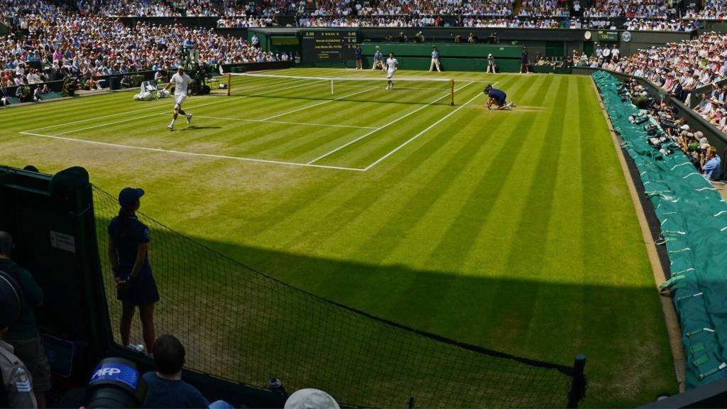 A tennis match being played on Centre Court at Wimbledon