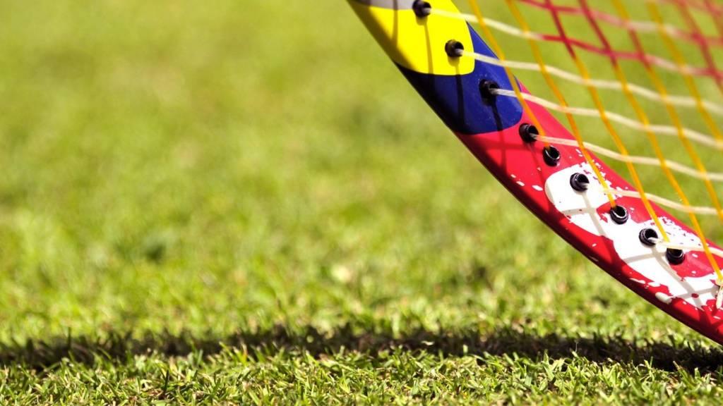 A close-up of a tennis racquet on a grass court at Wimbledon