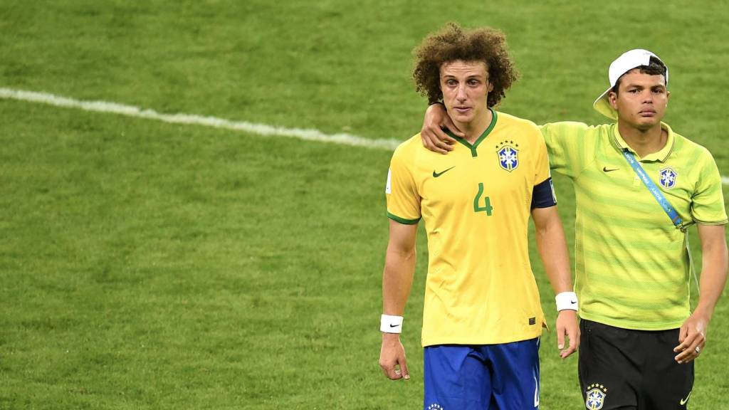 David Luiz is consoled by Brazil's defender and captain Thiago Silva