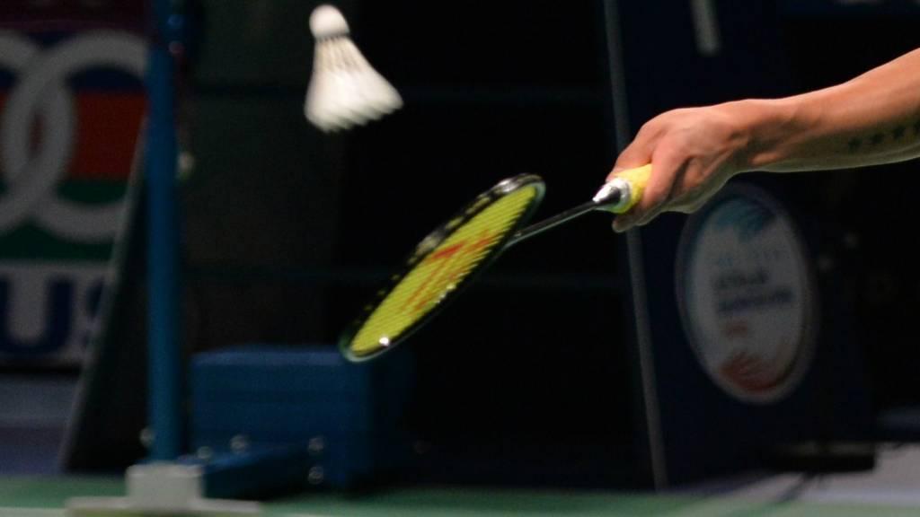 A badminton player hits the shuttlecock