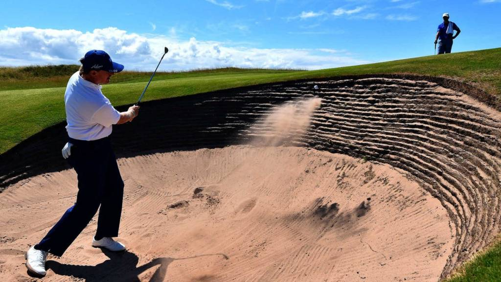 Ernie Els hits out of a bunker at the 2014 Open