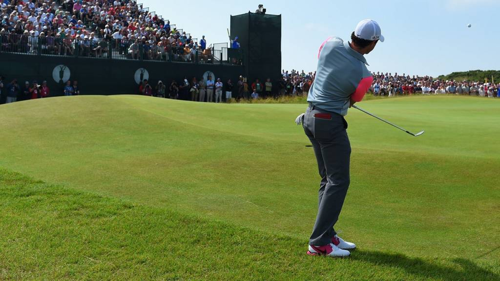 Rory McIlory at the Open stood in front of the leaderboard