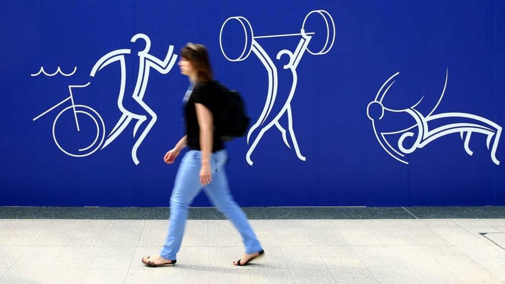 A fan walks past a Commonwealth Games billboard in Glasgow