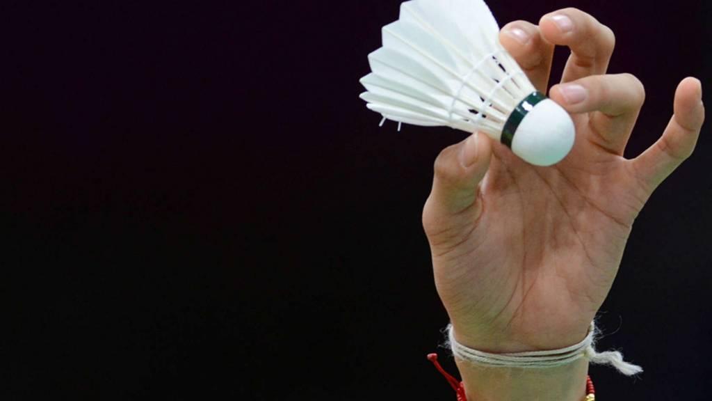 Badminton racket hitting a shuttlecock