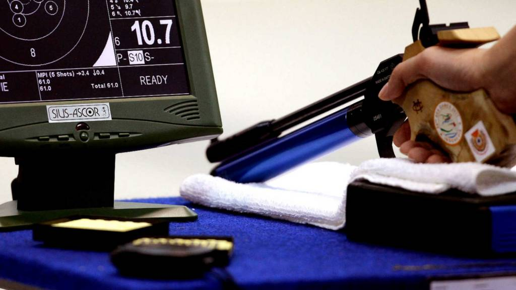 A shooter prepares their air pistol