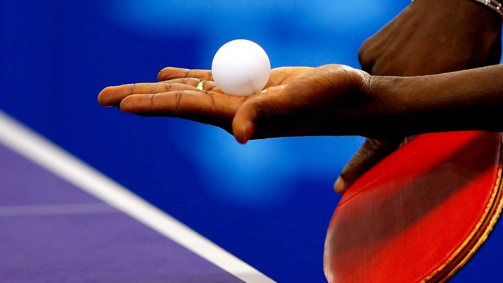 A table tennis player serves at Glasgow 2014