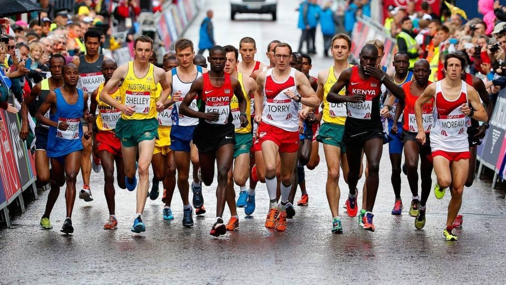 The men's marathon runners cross the start line