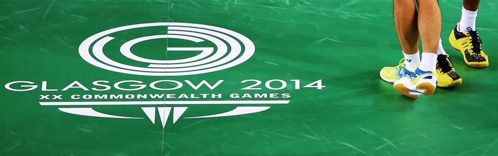 Doubles players stand by the Glasgow 2014 logo on court