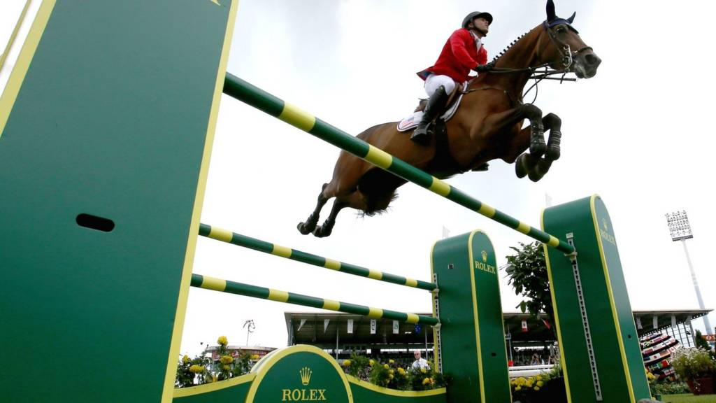 A rider jumps a fence at a showjumping event