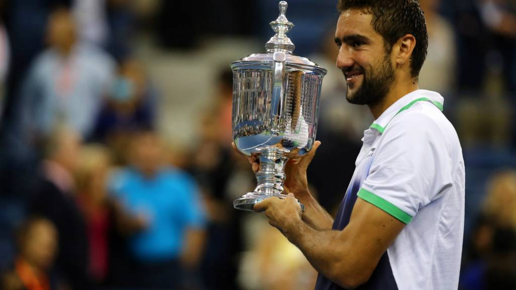 Marin Cilic of Croatia celebrates with the trophy after defeating Kei Nishikori of Japan to win the US Open men's singles final