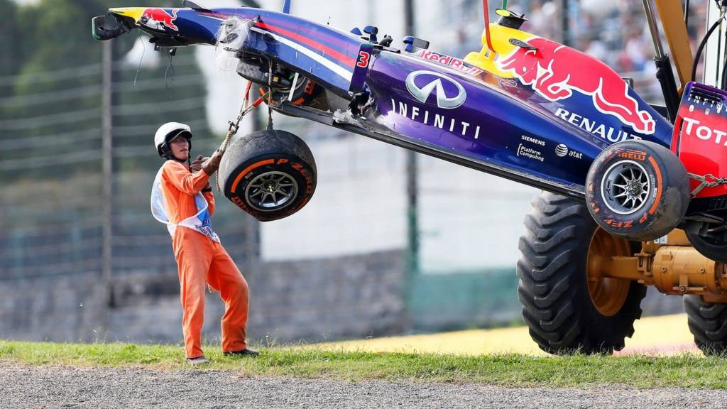 Marshalls remove the wrecked car belonging to Daniel Ricciardo