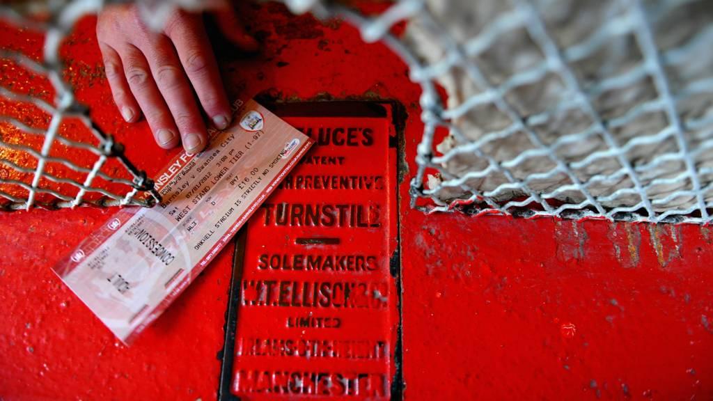 A fan hands over a ticket