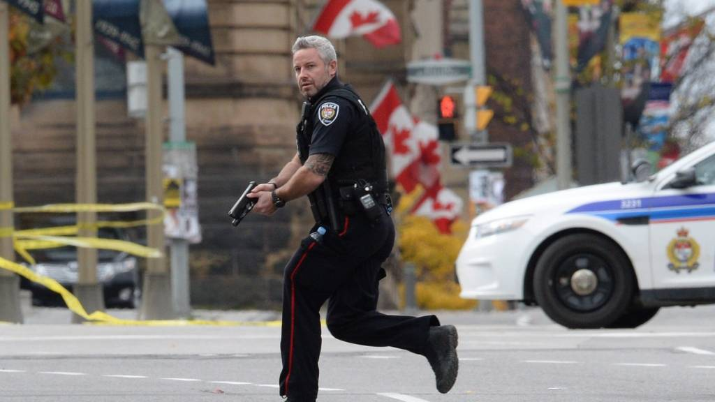 Police officer runs with weapon drawn outside parliament, Ottawa. 22 Oct 2014