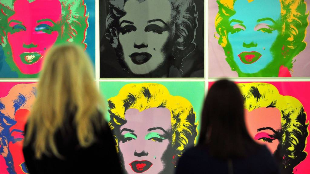 Gallery workers pose for pictures as they look at Andy Warhol's Untitled artwork of Marilyn Monroe at the Tate Liverpool