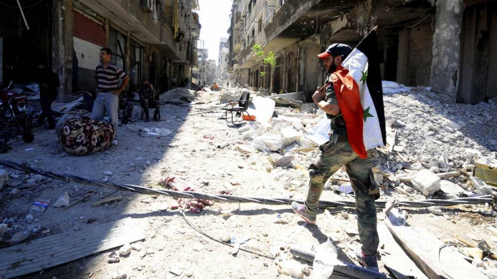 A man with a Syrian flag walks near destroyed buildings near Damascus. Photo: October 2014