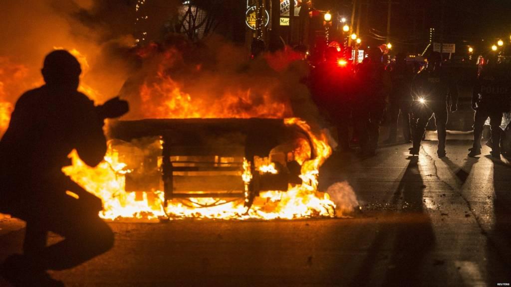Police near a burning vehicle in Ferguson