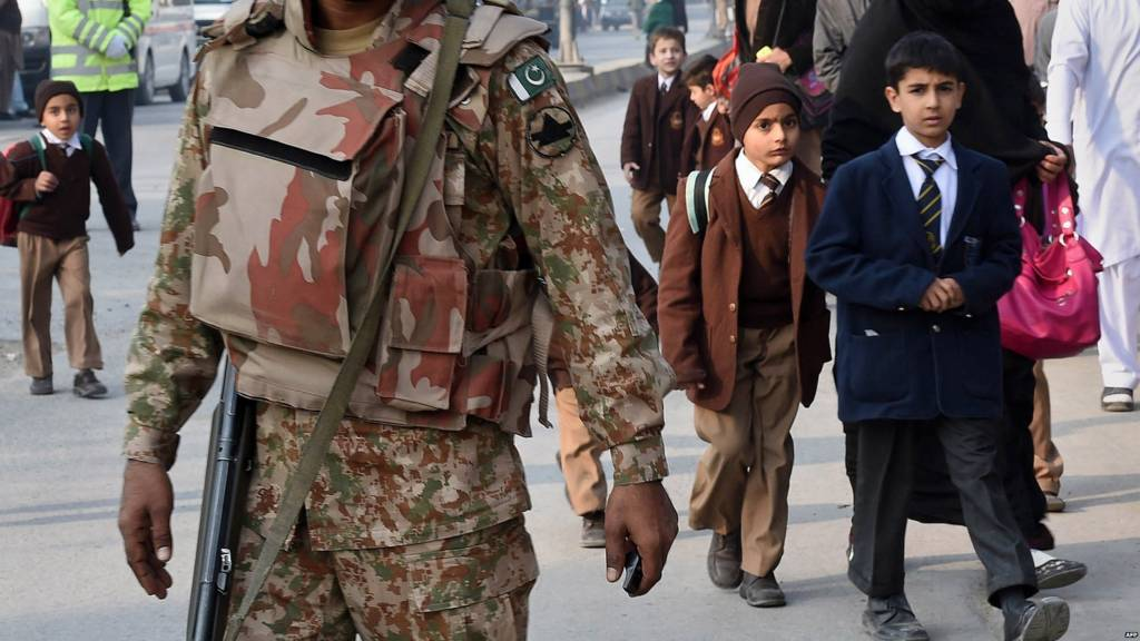 A Pakistani soldier stands guard as parents leave with their children near the site of an attack by Taliban gunmen on a school in Peshawar on 16 December 2014
