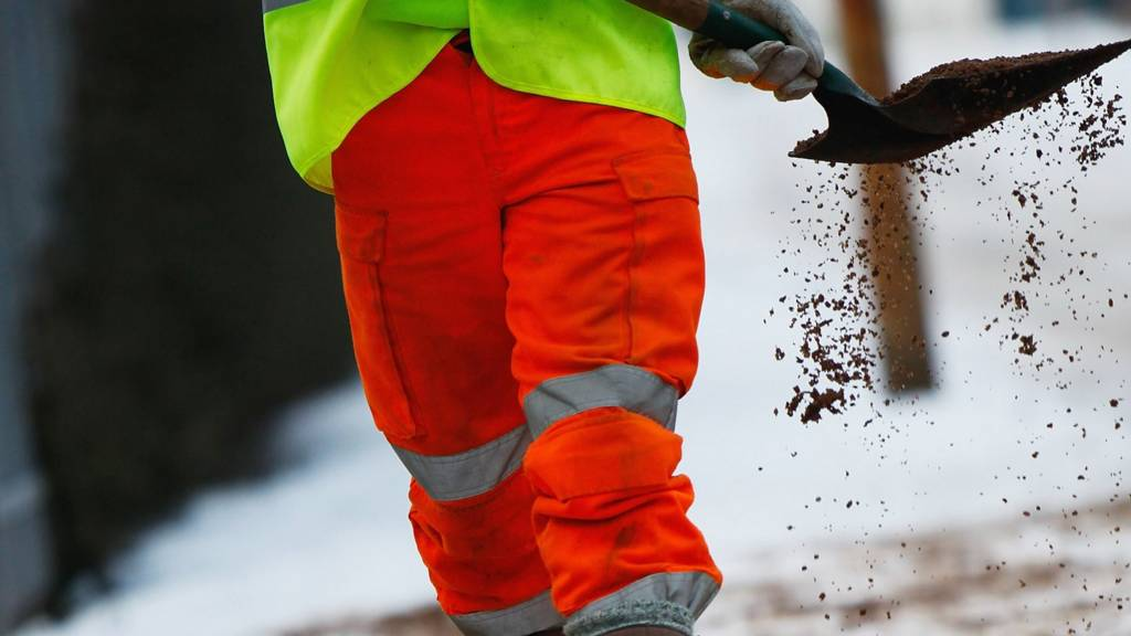 Council worker gritting road