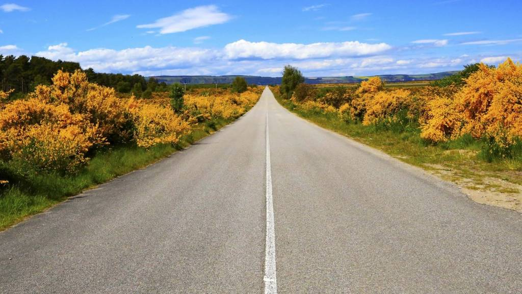 Blue sky over a long, straight road in Inverness