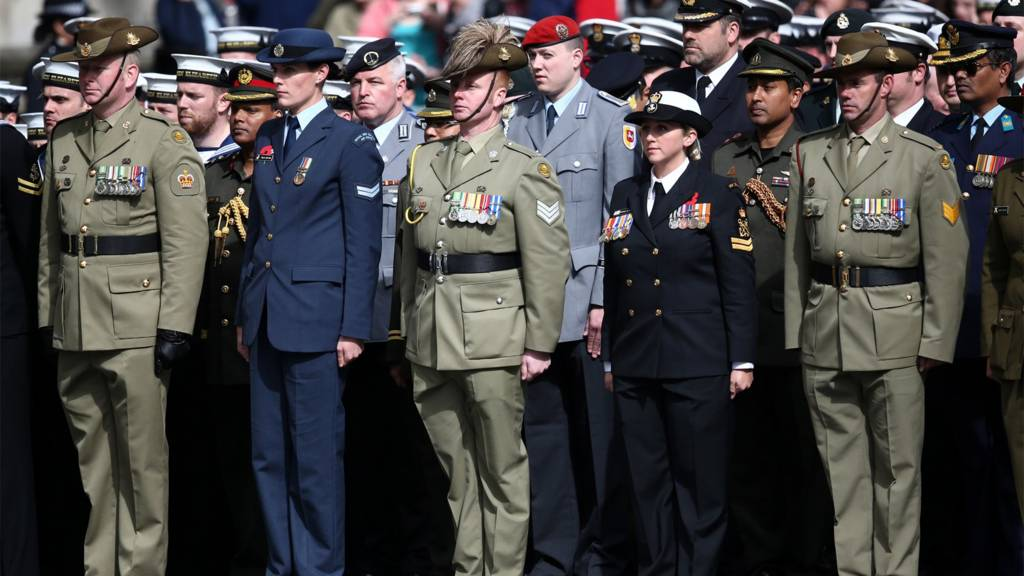 Members of the military stand during a ceremony at the Cenotaph