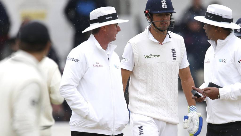 Alastair Cook talks to the umpires
