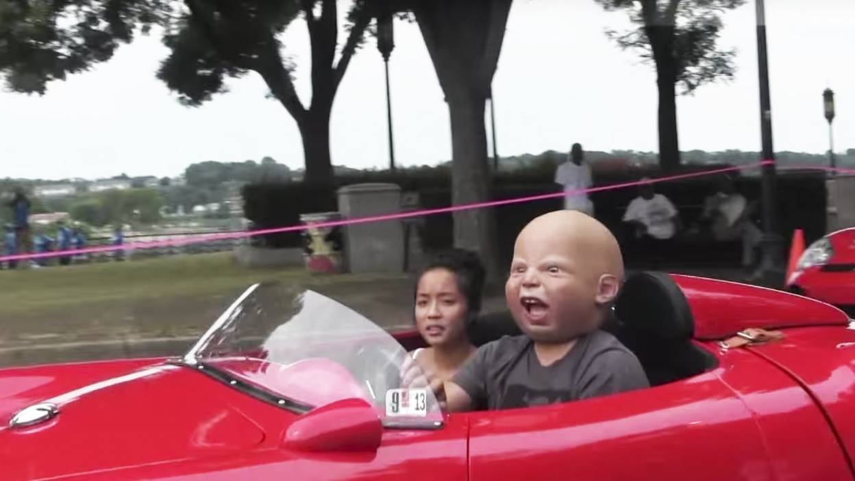 Someone driving a porsche with a baby mask on