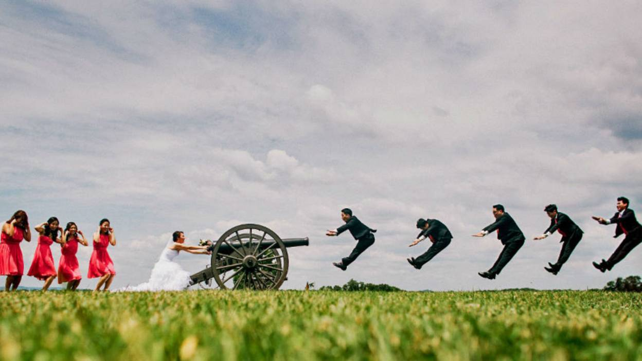 Staged photo of bride shooting groom with canon