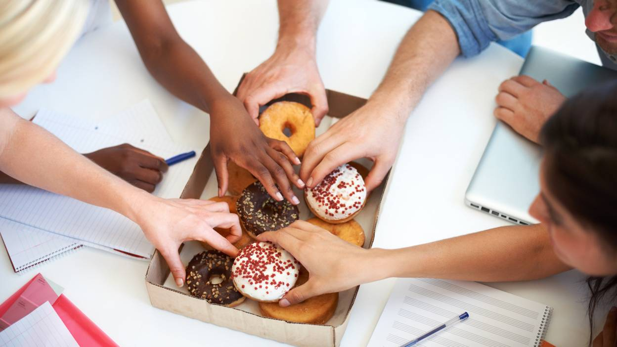 Colleagues reaching for donuts