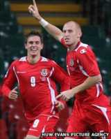 James Collins celebrates a goal versus Russia with Aaron Ramsey