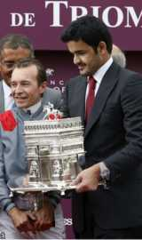 """French Jockey Thierry Jarnet (left) and owner of his horse Treve, Sheikh Joaan Bin Hamad Al Thani of Qatar receive a trophy on the podium after winning the Qatar Prix de l""""Arc de Triomphe"""